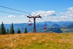 Chairlift on mountain meadow Royalty Free Stock Photos