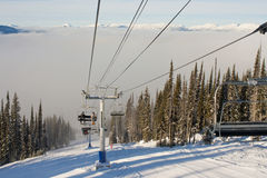 Chairlift at Mountain Ski Resort. A chairlift in Revelstoke, BC, Canada during a meteorological inversion where the cloud tops hang low in the valley Royalty Free Stock Images