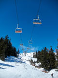 Chairlift with orange seats on blue sky. Snow-covered mountain Stock Photos