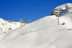 Chairlift over a snowy mountain. Chairlift at a ski resort over a snow covered mountain Stock Photo
