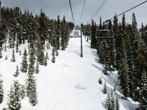 Chairlift på en lutning av en skidasemesterort under grå himmel Royaltyfria Foton