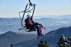 Chairlift with people at Stowe Ski Resort in Vermont, view to the Mansfield mountain slopes