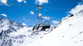 Chairlift seat. Against snowy Alpine mountains Stock Photo