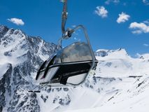 Chairlift seat. Against snowy Alpine mountains Stock Photos