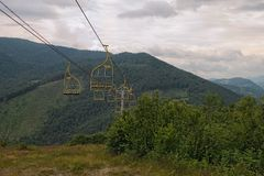 Chairlift ski lift in Carpathian mountains leading from mountain station. Transporting hikers in summer season. stock image