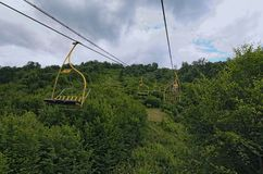 Chairlift ski lift in Carpathian mountains leading to mountain station. Transporting hikers in summer season. Royalty Free Stock Photo