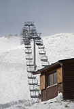 Chairlift in a ski resort. With a wooden hut at the bottom Royalty Free Stock Photos
