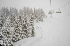 Chairlift in snowfall at alpine ski resort Royalty Free Stock Photography