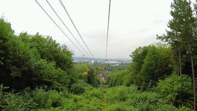 Chairlift from summer mountain to city stock footage