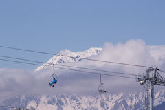 Chairlift in the winter mountains. Chairlift in snowy mountains above the clouds Royalty Free Stock Image