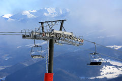 Chairlift on winter ski resort against mountain Background Stock Photo