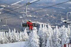 Free Chairlift With One Person Wearing Red Ski Suit At Stowe Ski Resort In Vermont, View To The Mansfield Mountain Slopes Royalty Free Stock Photos - 205924288