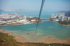Chairlifts above the water. On a background of mountains and the city stock images