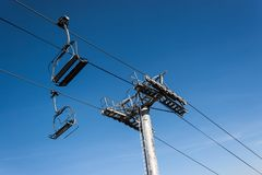Chairlifts on a blue clear ski during on a bright day.  Stock Photos