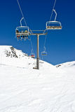 Chairlifts to the top. Chairlift taking skiers to the top of an alpine slope Stock Image