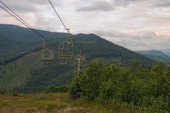 Chairliftskidlift i Carpathian berg som leder från bergstation Transportering av fotvandrare i sommarsäsong fotografering för bildbyråer