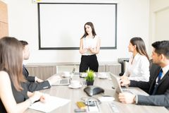 Chairman And Clients Working On Project In Meeting. Female business leader sharing project details with clients during meeting in office royalty free stock photography