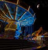 Chairoplane op een festival met blauwe lichten en de maan op achtergrond stock afbeeldingen