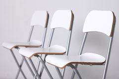 Chairs. White high chairs in a row royalty free stock photos
