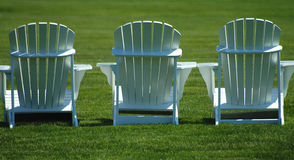 Chairs. A row of three lawn chairs on a vividly green lawn royalty free stock images