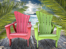 Chairs. Two wooden colorful chairs on a weathered wooden deck by the beach. Palm fronds frame the image royalty free stock images