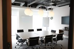 Chairs Around Boardroom Table In Empty Modern Meeting Room stock images
