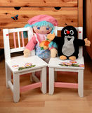 Chairs and baby dummies. Two baby dummies sitting on baby chairs stock image