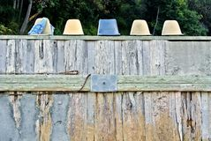 Chairs on beach wall. Row of old plastic chairs on top of a wood beach wall Stock Photo