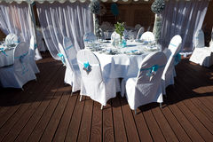 Chairs with blue ribbons on the wedding celebration  the outdoor deck Royalty Free Stock Photos