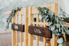 Chairs for bride and groom decorated with flowers with signs mr and mrs for wedding ceremony