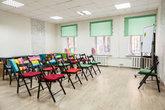 Chairs with colored capes in hall for seminar or meeting Stock Photo