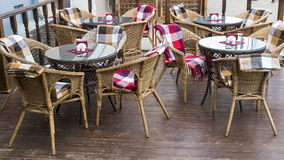 Chairs with colorful rugs and tables on the terrace of a street Stock Photos