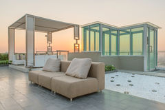 Chairs and a couch provide a place from a highrise rooftop.  Stock Images