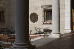 Chairs in the courtyard of the Boston Library. Three chairs and a table are awaiting guest in the courtyard of the Boston Library. Red bricked floor and large royalty free stock photo