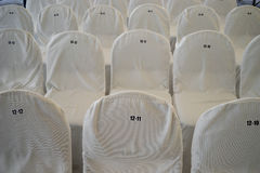 Chairs, covered with white bedspreads with numbers Stock Photography