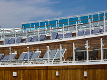 Chairs on deck. Blue striped chairs on the deck of cruise ship Stock Image