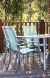 Chairs on decking in summer light. With trees in the background stock image
