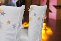 Chairs decorated in a banquet hall. Chairs decorated with stars in a banquet hall for wedding or party Royalty Free Stock Photography