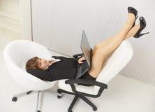 chairs den roliga bärbar dator lokaliserade kontorskvinnan Arkivfoto