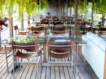 Chairs and dining glass tables on wooden floor, restaurant interior stock photo
