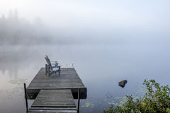 Chairs on a Dock Overlooking a Lake in the Early Morning Mist - Royalty Free Stock Images