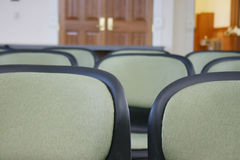 Chairs and doors. Close-up view of row of chairs in meeting area Stock Photos