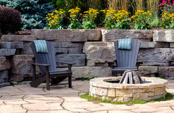 Chairs and fire-pit patio. Natural wood adirondack chairs sit around a stone fire-pit, in a beautiful patio garden filled with flowers Royalty Free Stock Images