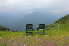 Chairs in front of the mountain. Chairs in a meadow in front of the mountain Stock Image