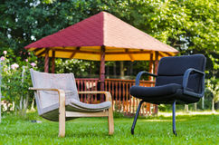 Chairs in garden. Two empty chairs on the lawn with rustic wood pavilion in the background Stock Images