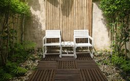 Chairs in the garden. Two wooden chairs in the white garden Royalty Free Stock Image