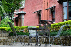 Chairs in a hedged area with brick wall Stock Photo