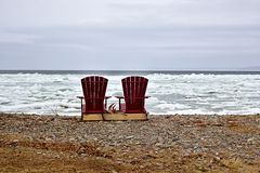 Chairs on icy lake  royalty free stock photography
