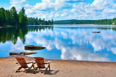 Chairs lake shore. Two wooden deck chairs on the shore of a lake in Canada with clouds reflecting on the water Royalty Free Stock Image