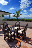 Chairs and little table on a tropical terrace overlooking the sea Stock Photography